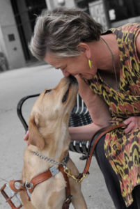 Author Beth Finke smiling and giving her Seeing Eye dog a smooch